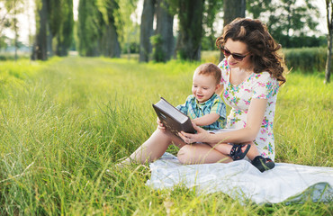 Mother with curly hairstyle reading fairy tales for baby