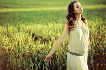 Pregnant woman walking on the corn field