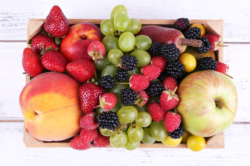 Different berries and fruits in box on wooden table close-up