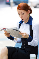 Shocked businesswoman reading newspaper outside office