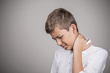 teenager with back neck pain isolated on grey background