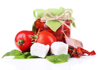 Sun dried tomatoes in glass jar, feta cheese and basil leaves