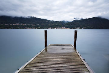 Tranquil scene of old wooden pier and misty Italian Alps mountai