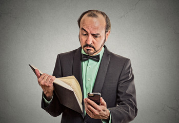 skeptical man reading news on smartphone, holding book
