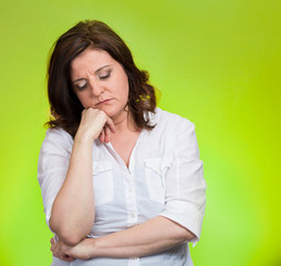 Portrait depressed gloomy woman on green background