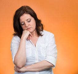 Portrait depressed gloomy woman on orange background
