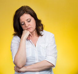 Depressed, gloomy woman isolated on yellow background