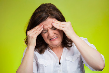Stressed  woman with headache on green background