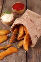 Homemade fried potato in paper bag, on wooden background