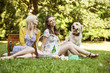 Two girlfriends with dog on the picnic