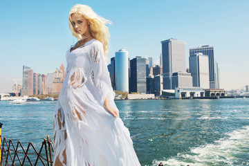 Woman wearing ragged dress with the city in the background