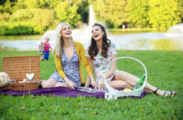 Two girlfriends laughing during picnic