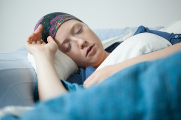 Young woman having tumor sleeping
