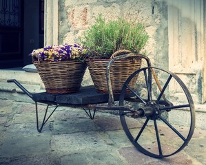 old wheelbarrow with baskets of flowers