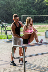 Fitness coach helping attractive woman