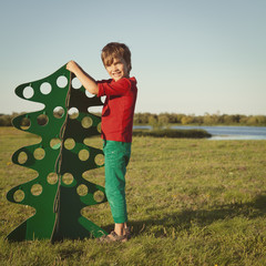 happy boy playing with paper tree