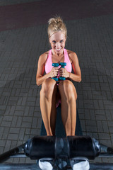 Smiling girl exercising on incline bench