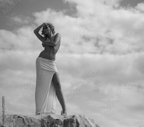 canvas print picture Half-naked woman looking at the rocks