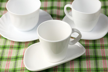 Three white empty cups and saucers on green background.