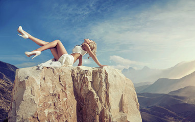 Sensual blonde relaxing on the rock