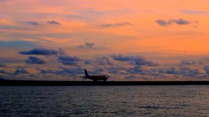 Airplane (Aeroplane) Taxing Along Runway at Dusk