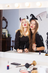 Funny girls doing makeup for a Halloween