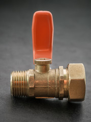 Ball valve with red handle on dark background.