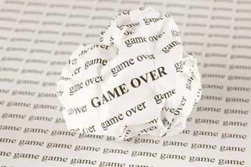 Crumpled paper ball with words Game Over
