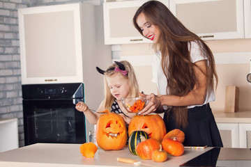 Kid on Halloween party making carved pumpkin with a little help