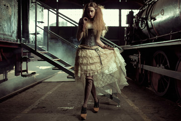 Young dressed woman in the empty railway station