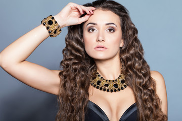 Fashion model with long curly hair. Fashion model in studio