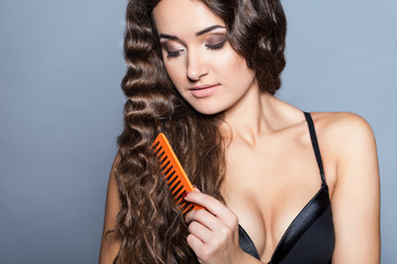 Woman Portrait. Curly Hair and Comb in studio