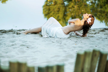 Alluring woman lying on the white sand
