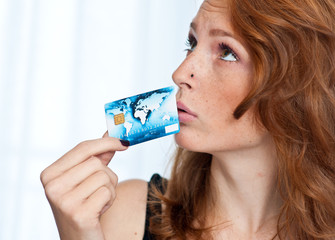 freckled woman holding credit card