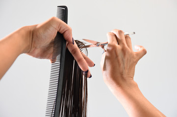 Close up of beautician's hand with a comb cutting hair of woman