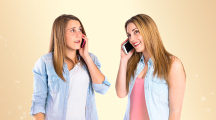 Young girls talking to mobile over gloss background