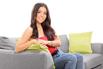 Young beautiful girl posing seated on a sofa