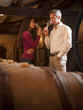 Couple smelling a glass of white wine in his traditional cellar