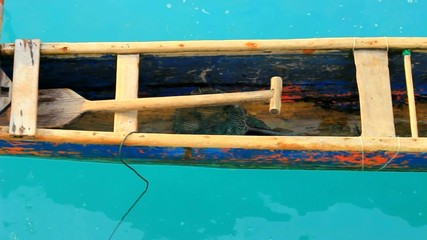 Rustic Traditional Canoe Floating in an Aqua Tropical Ocean