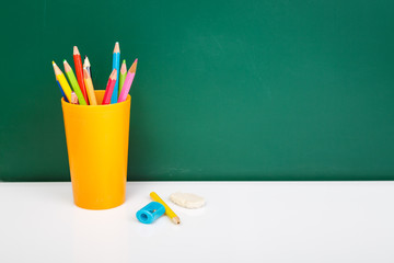 Colorful used pens in yellow glass on white desk against green c