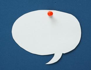 Blank white paper speech bubble on a blue notice board