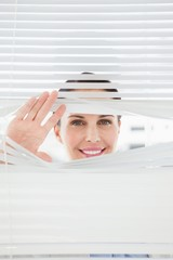 Woman looking out through blinds