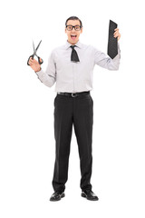 Man holding a piece of his tie and scissors