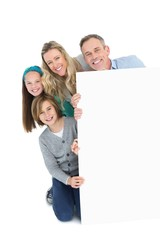 Cute family smiling at camera holding poster