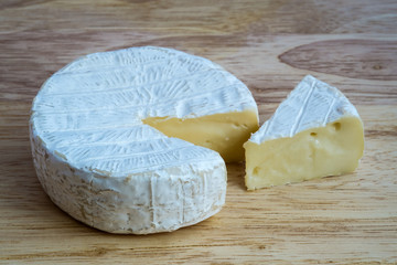 Camembert cheese on wooden table