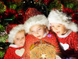 Three little girls in Santa hats looking on christmas house