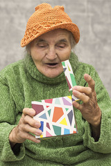 Happy and surprised elderly woman after opening gift box.