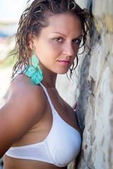 Beautiful girl in bikini  stands near the stone wall