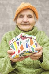 Elderly woman holding a gift box.