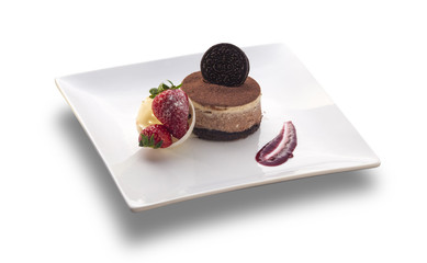 chocolate cake round with cookie on the top and strawberry